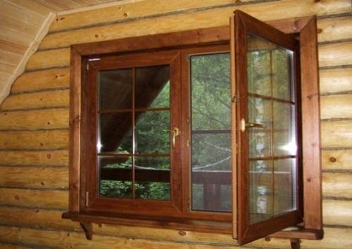 Пластиковое окно коричневого «древесного цвета» естественно смотрится в бревенчатой стене