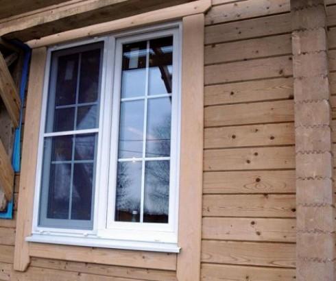 Брусовый дом с белым пластиковым окном и деревянными наличниками (бросается в глаза цветовой диссонанс между белым пластиком и натуральным деревом)
